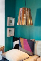 Upcycling - pendant lamp made from wooden rods above patchwork cushions