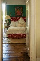 View through open door into bedroom with wooden floor and lace bedspread on red bed