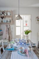 Pendant lamp above set dining table in vintage-style shabby-chic kitchen-dining room