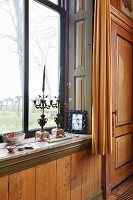 Ornate vintage candlesticks on sill of window with garden view