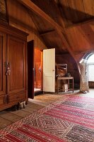 Bedroom in wood-panelled attic room with ethnic rug, wardrobe, tailors' dummy and dressing table