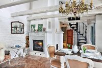 White upholstered chairs around dining table set for afternoon coffee in front of fireplace in renovated country house