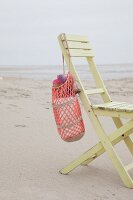 Crocheted beach bag hanging on wooden chair on beach