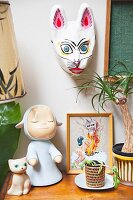 Retro toys, doll and cat ornament next to house plant and below animal mask