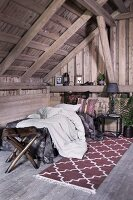 Bed with pale bed linen, stool with animal-skin seat, patterned rug and exposed roof structure in rustic attic room