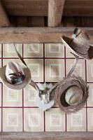Various hats hung from antlers on wallpapered wall