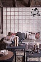 Candles and books on metal side table; cushions on comfortable bench against wall covered with vintage-style wallpaper
