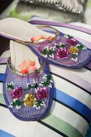 Indian-style purple slippers embroidered with sequinned flowers on striped cushion