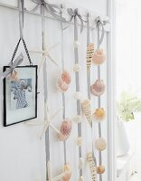 Seashells stuck on ribbons and hung from hooks