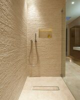 Walk-in shower in designer bathroom with natural-effect tiles; shelf niche with indirect lighting in back wall