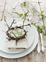 Spring place setting decorated with flowering twigs and small wreath