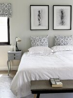Double bed with white bed linen and black and white patterned pillows; vintage bedside cabinet and black-framed pictures against pale grey wall