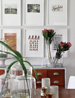 Leaves in vintage glass vessels, tropical flowers in glass vase on sideboard and gallery of pictures on wall