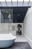 Elegant minimalist bathroom with glass-brick wall and designer bathtub