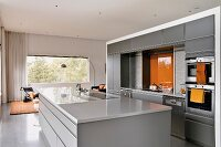 Open-plan modern kitchen in pale grey with orange accents