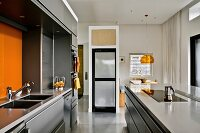 Modern kitchen in pale grey with orange accents