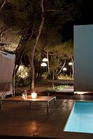 Romantic seating area next to illuminated swimming pool at night