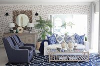 Blue and white living room with mixture of patterns on wallpaper, cushions and rug
