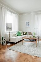 White leather sofa with patterned scatter cushions, coffee table and standard lamp in living room