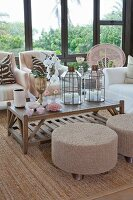 Pouffes at coffee table with candle lanterns and vases of flowers in conservatory