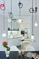 Pendant lamps above tables in front of open doorway with view of counter in open-plan fitted kitchen