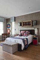 Vintage-style teenager's bedroom with Union-Flag scatter cushions on bed and old wooden trunk at foot