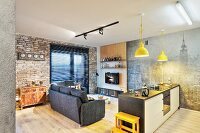 Kitchen counter and sofa in open-plan interior with brick wall and photo mural