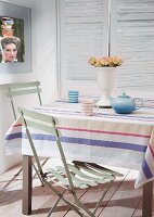 Teapot and mugs on table with striped tablecloth and pale green folding chairs