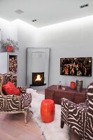 Zebra-print armchairs and orange, drum-shaped side table in room with corner fireplace and suspended ceiling