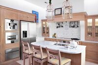 Breakfast bar and bar stools in open-plan kitchen with pale wooden cabinet in modern, country-house style