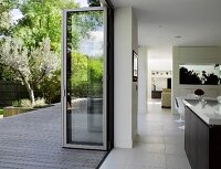 View from open-plan interior through open folding door out onto terrace and into garden