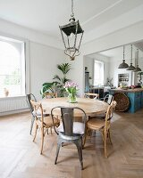 Round dining table, various chairs and lantern-style lamp with open-plan kitchen in background