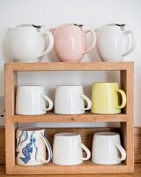 Retro teapots and mugs on wooden shelves