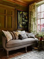 Rococo sofa with grey cover, curtain with botanical patterns and illustrations of plants on spring roller screen