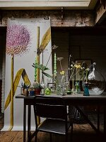 Various vases of flowers on table in front of poster of allium flower