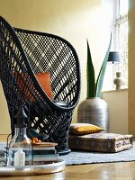 Peacock chair, ethnic floor cushion and agave leaves in African vase