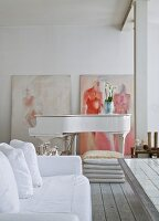 Sofa with white loose cover and grand piano in open-plan living area with modern paintings leaning against whitewashed brick wall