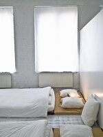 Japanese-style sleeping area with white curtains on windows and whitewashed brick wall