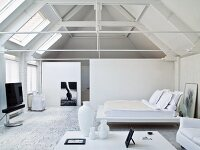 Elegant, white bedroom with exposed roof structure