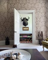 Coffee table in traditional living room with ornate wallpaper and view through open door of water buffalo hunting trophy on wall