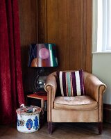 Striped cushion on pale brown leather armchair and table lamp with patterned lampshade on side table in corner of wood-clad room