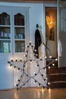 Star-shaped lamp with light bulbs on wire frame leaning against fitted cupboard in rustic interior