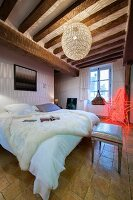 White fur on double bed below spherical lamp and red star-shaped lamp in background in elegant, rustic bedroom with wood-beamed ceiling