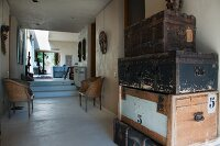 Stack of old steamer trunks in foyer of bungalow with view into interior
