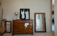 Picture of camisoles on top of antique chest of drawers next to floor-standing mirror