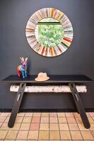 Round mirror with colourful frame and dark wooden table against black wall