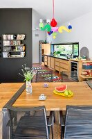 Dining table with wooden top mounted on metal frame, black metal chairs and pendant lamp with colourful arms in open-plan interior