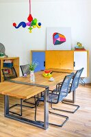 Dining table with wooden top mounted on metal frame, metal cantilever chairs, postmodern pendant lamp and sideboard with colourful doors in background