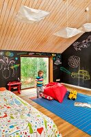 Little boy next to red beanbag on blue rug, chalkboard walls with chalk drawings and wood-clad ceiling in child's attic bedroom