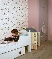 Girl lying on bed reading in child's bedroom with bird-patterned wallpaper, dolls' house and fitted wardrobe